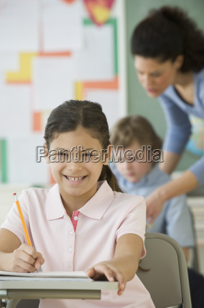 hispanic girl writing at school desk