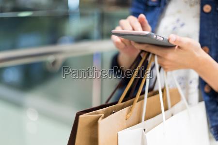 einkaufsfrau die mobiltelefon verwendet