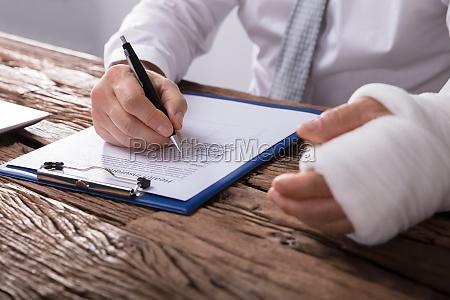 homem com braco quebrado preenchendo formulario