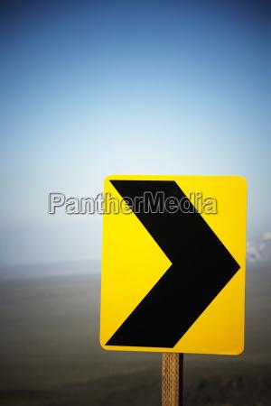 um sinal amarelo da seta do