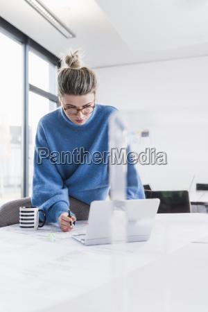 mujer joven con ordenador portatil y