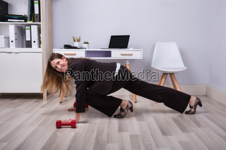 businesswoman doing pushups