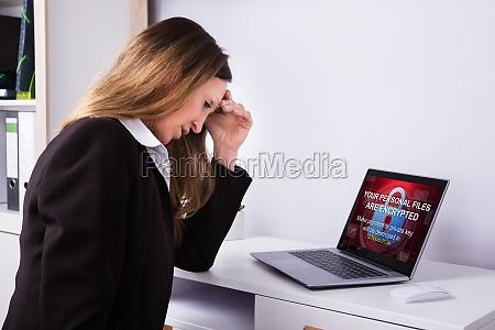 upset businesswoman sitting in office
