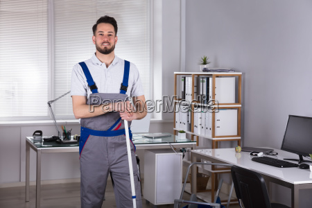 male janitor standing with broom in