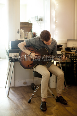 man practicing guitar at home