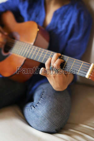 midsection of woman practicing guitar while