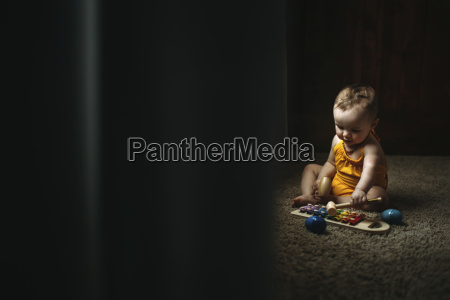baby girl playing xylophone while sitting