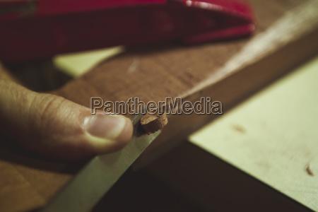 cropped finger of man shaving wood