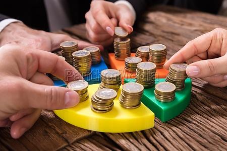 businesspeople que empilham moedas na carta