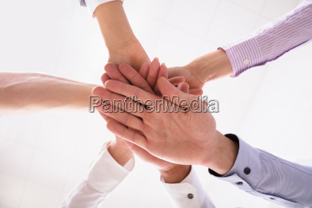 close up of businesspeople stacking hands