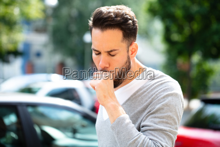 man coughing at outdoor