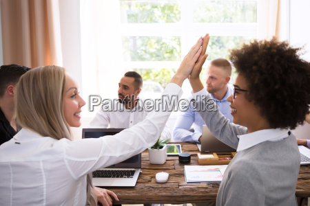 two businesswomen giving high five
