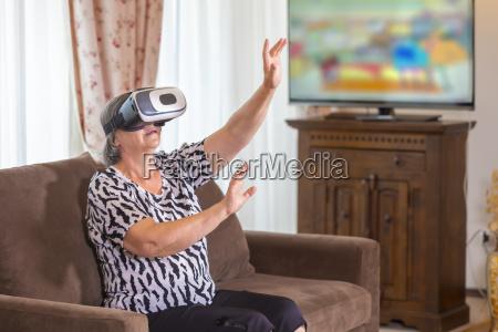 mulher senior com auriculares virtuais ou