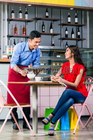 garcom bonito servindo cafe na mesa