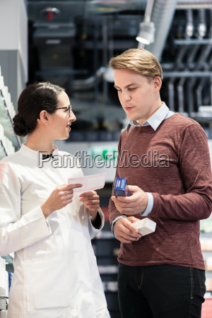 young man holding two medicines while