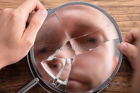 face do homem no espelho quebrado