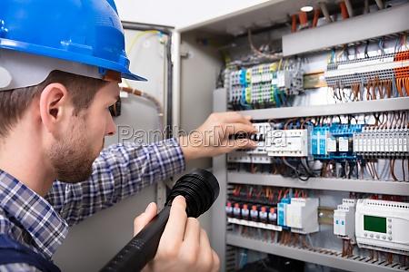 eletricista que examina uma caixa de