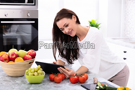 mulher feliz que usa a tabuleta