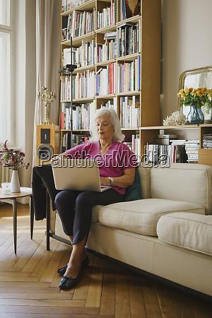 idosa usando laptop no sofa da