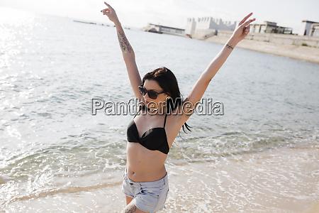 happy young woman walking at seashore