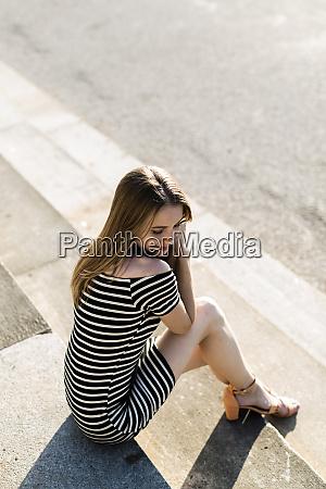 young woman wearing striped dress relaxing