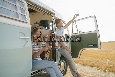 jovem casal com celulares relaxando em