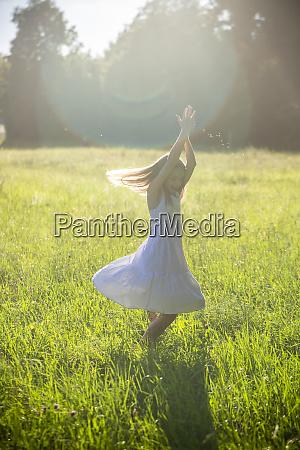happy girl dancing on summer meadow