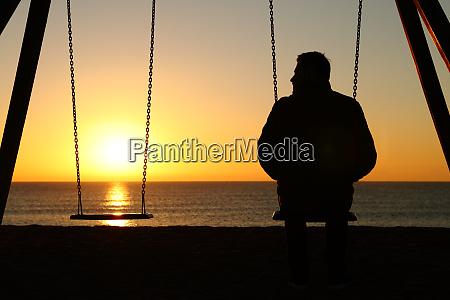homem sozinho em um balanco olhando