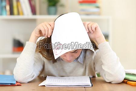 aluno triste com um exame reprovado