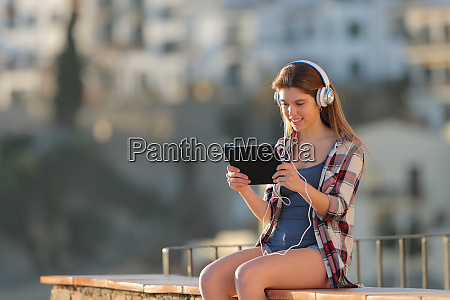 happy teen listening and watching tablet