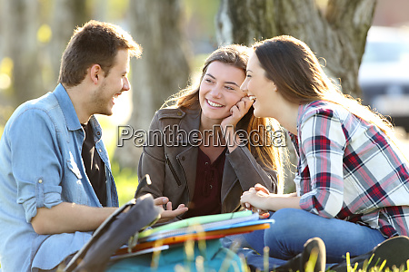 three students talking after classes outside