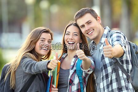 tres estudantes felizes com polegares acima