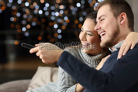 funny couple watching tv at home