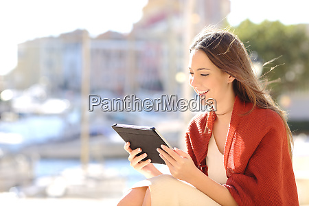 woman using a tablet watching media