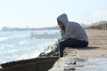 menina adolescente triste sozinha na praia