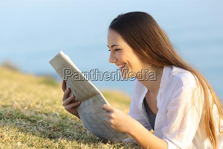 happy woman reading a newspaper lying