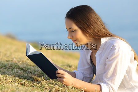relaxed woman reading a paper book