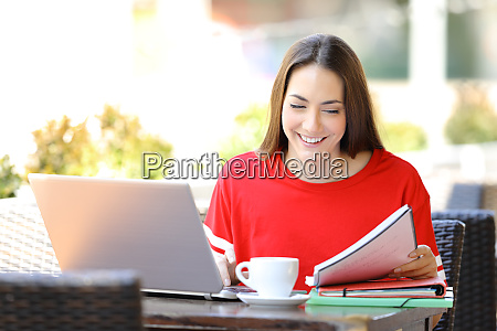 happy student with a laptop studying