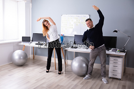 businesspeople standing in office doing exercise