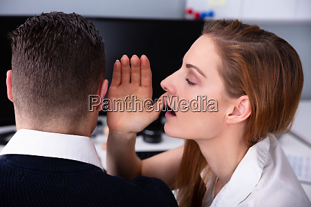 businesswoman whispering secret into male colleagues