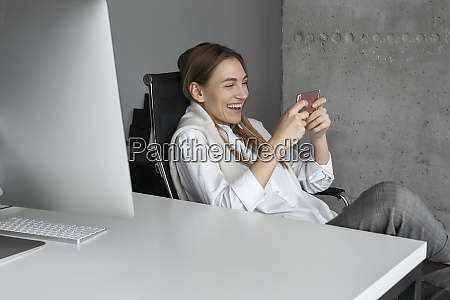 laughing businesswoman using smartphone at desk