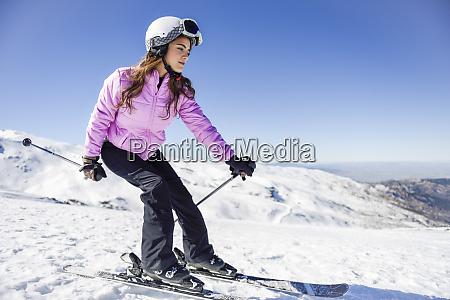 mulher esquiando sob ceu azul sierra