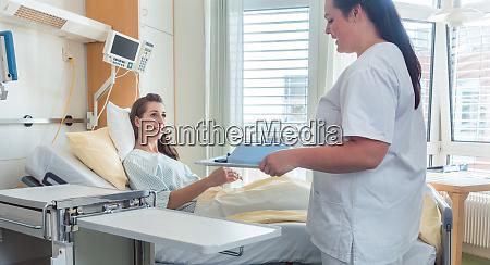 enfermeira trazendo refeicao paciente mulher na
