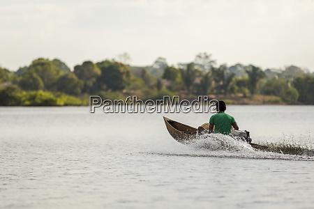 homem em canoa motorizada de madeira