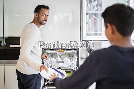 pai e filho na cozinha limpando