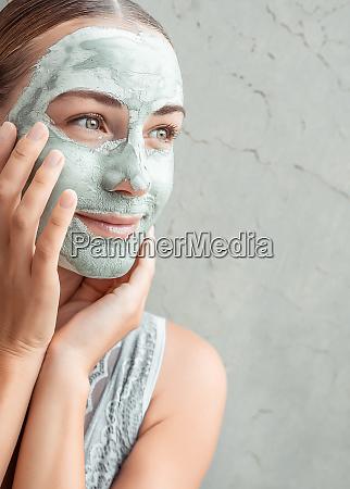 mulher feliz fazendo mascara de argila