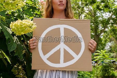 mulher segurando simbolo de paz por