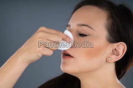woman trying to stop nose from