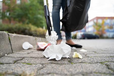 mulher coletando lixo ao ar livre