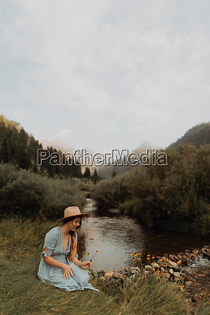 young woman sitting picking wildflowers by